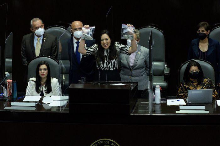 """Cynthia Iliana López Castro, diputada del PRI, protesta en contra de la aprobación de la Ley Federal para la Regulación del Cannabis, mostrando dos bolsas de """"porros"""" simulados."""