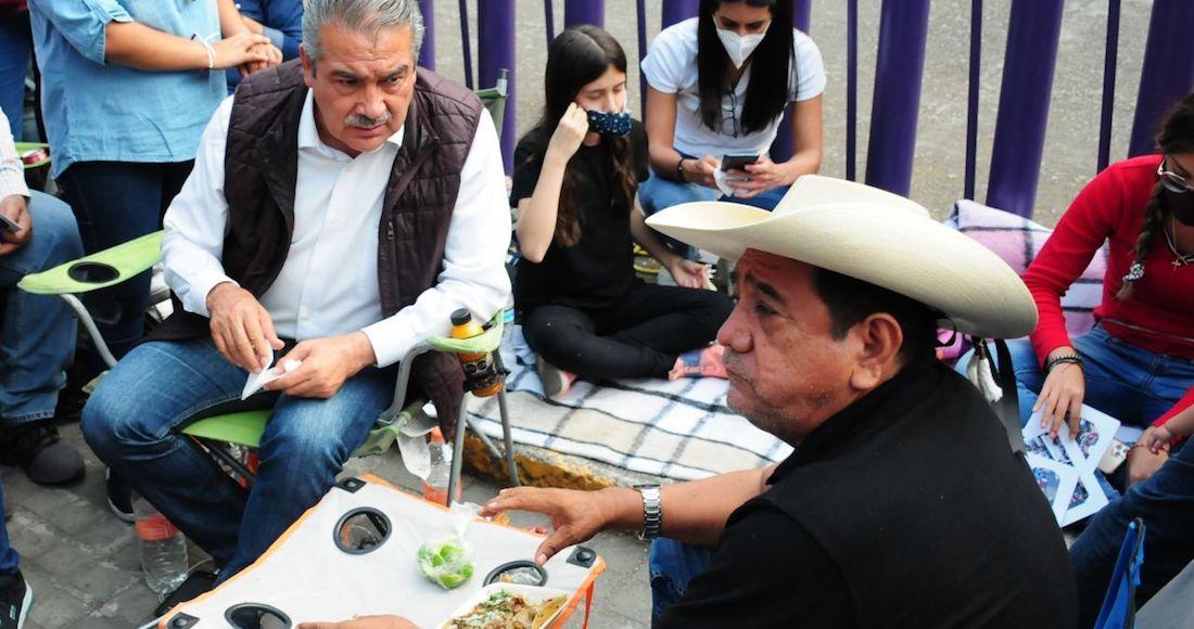 Raúl Morón y Félix Salgado Macedonio, comen durante el plantón afuera de las instalaciones del INE.